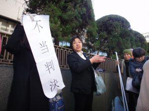 何もわからない傍聴者に、法廷の事情を説明する原告弁護団事務局長・大江京子弁護士。大法廷は傍聴者で埋め尽くされた。